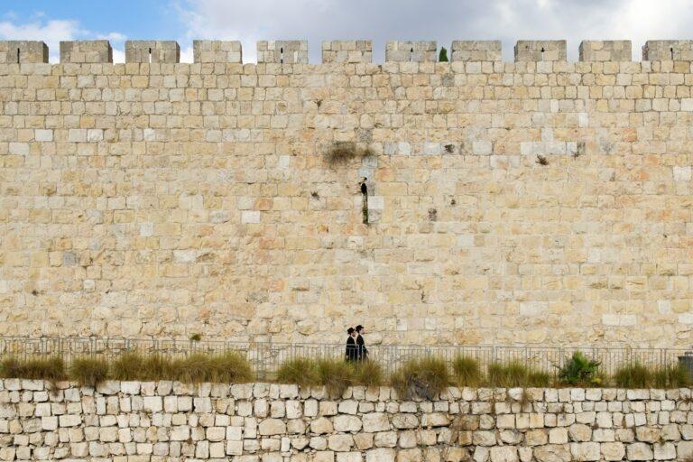 two person walking beside beige brick wall
