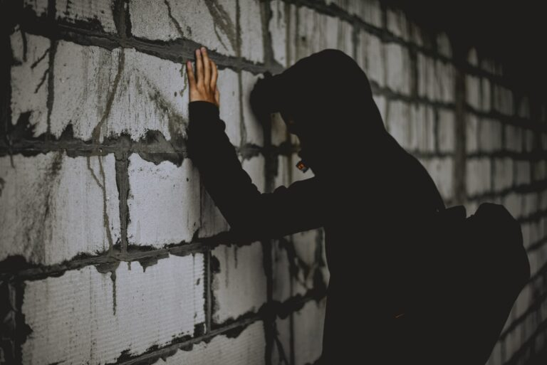man leaning on wall